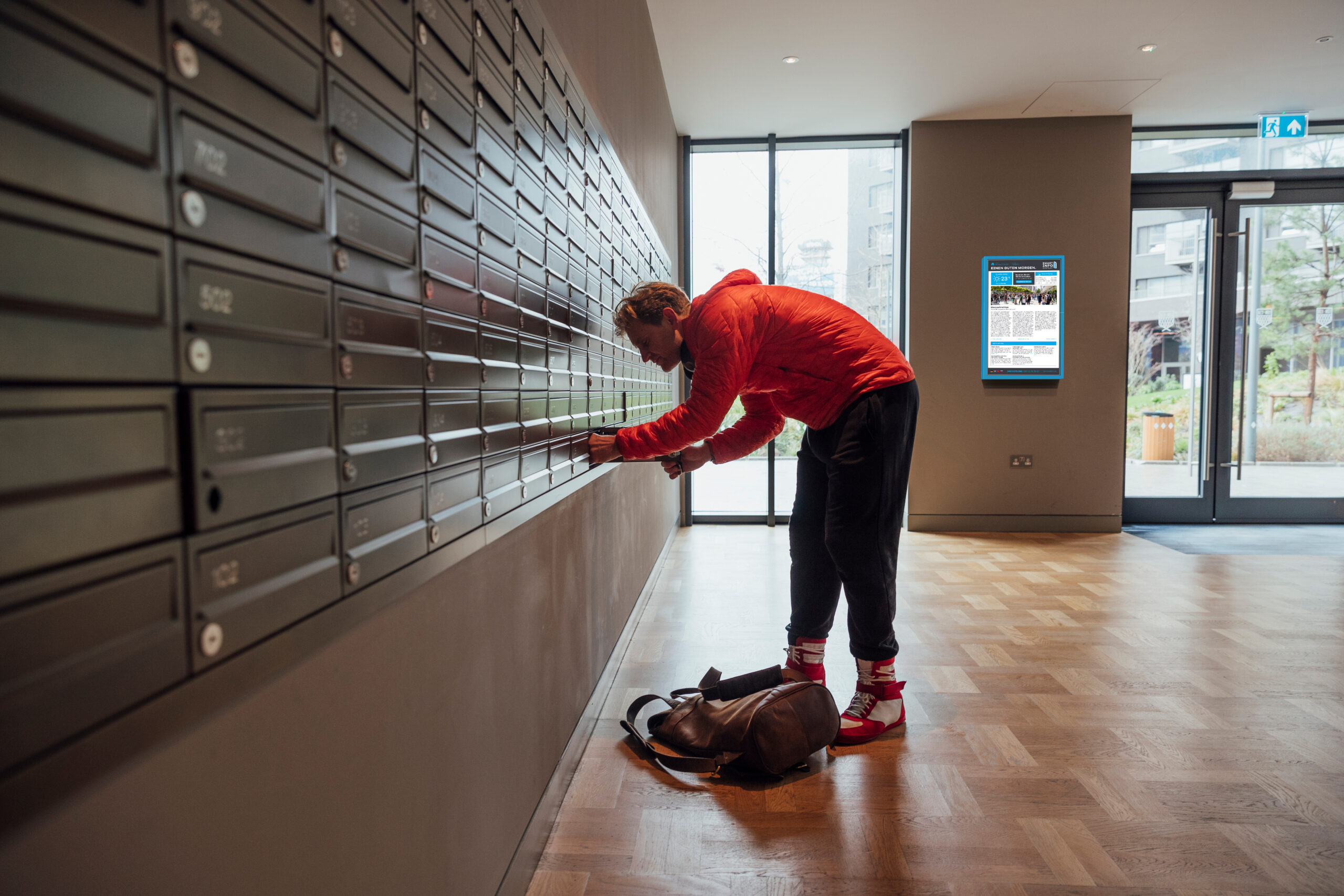 A side-view shot of a caucasian man unlocking his mailbox at his apartment in London, England.